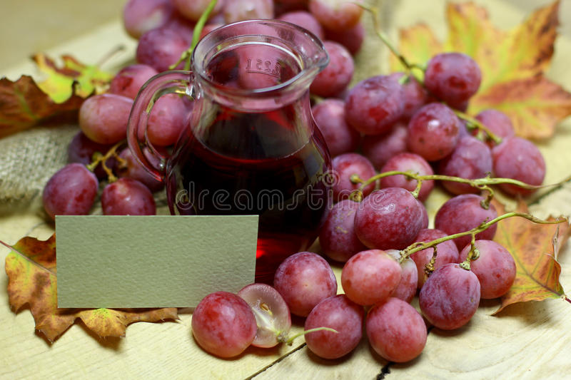 Natural grape red juice in glass jug and paper card label. Red rose grapes bunch, glass jug bottle with red wine, and autumn leaves on wood background design stock photos