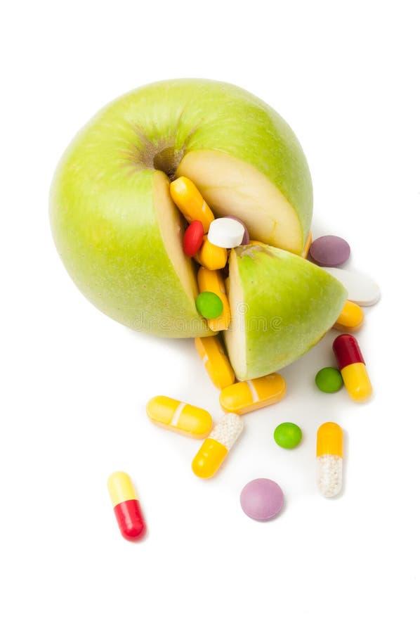 Natural green apple and various pills stock photography