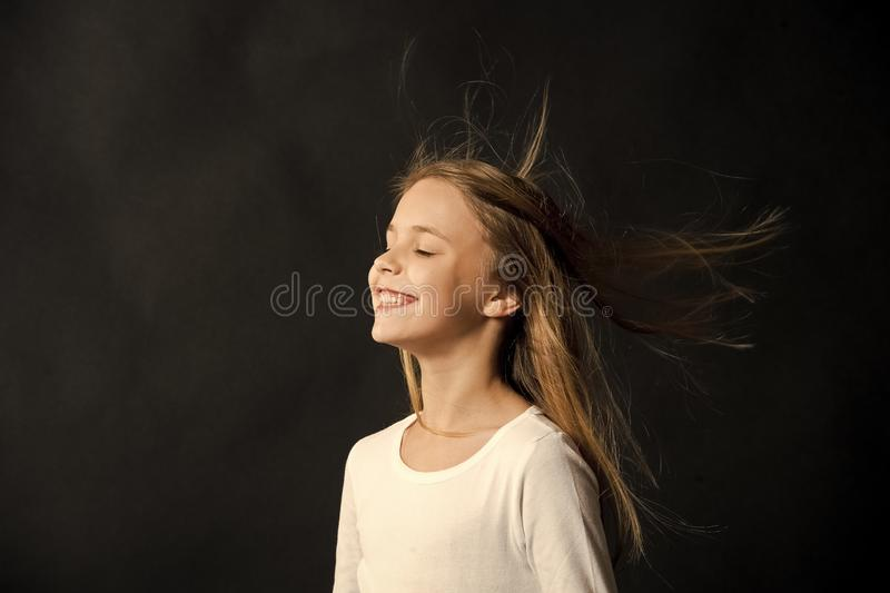 Natural hair. Girl kid long hair flying in air, black background. Child with natural beautiful healthy hairstyle stock images