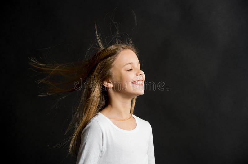Natural hair. Girl kid long hair flying in air, black background. Child with natural beautiful healthy hairstyle stock photos