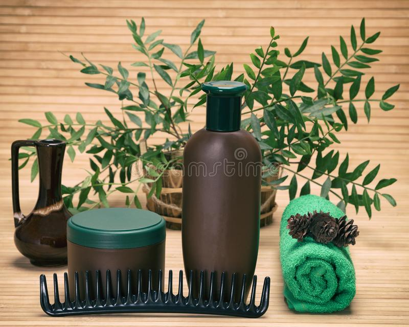 Natural hair treatment products. Comb and towel with coniferous cones against the background of green plant branches in wooden basket stock photos