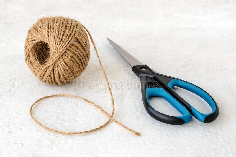 Natural hemp cord ball and scissors on a rough white surface. Roll of jute string or flax twine. Coarse rustic thread for stock photography