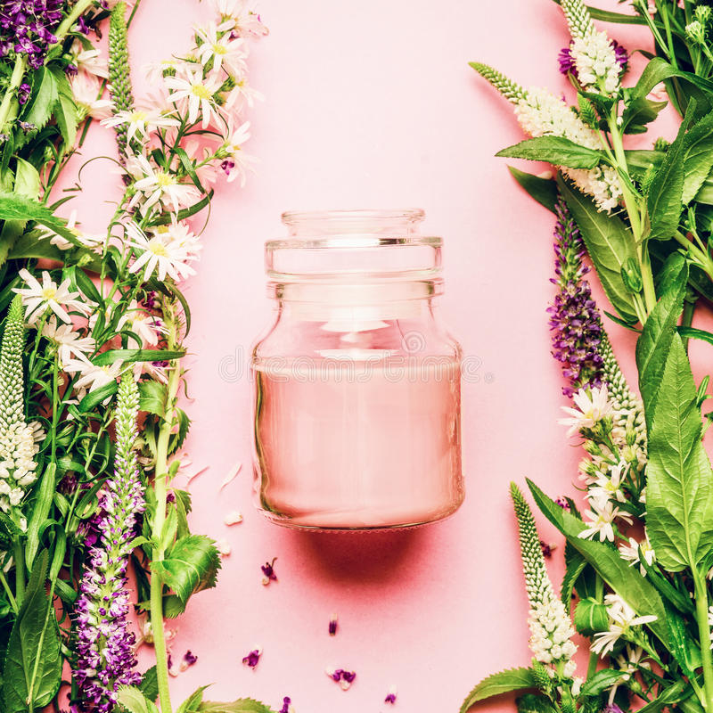 Natural herbal skin care cosmetic concept. Glass jar with cream and fresh herbs and flowers on pink background, top view, copy spa stock photo