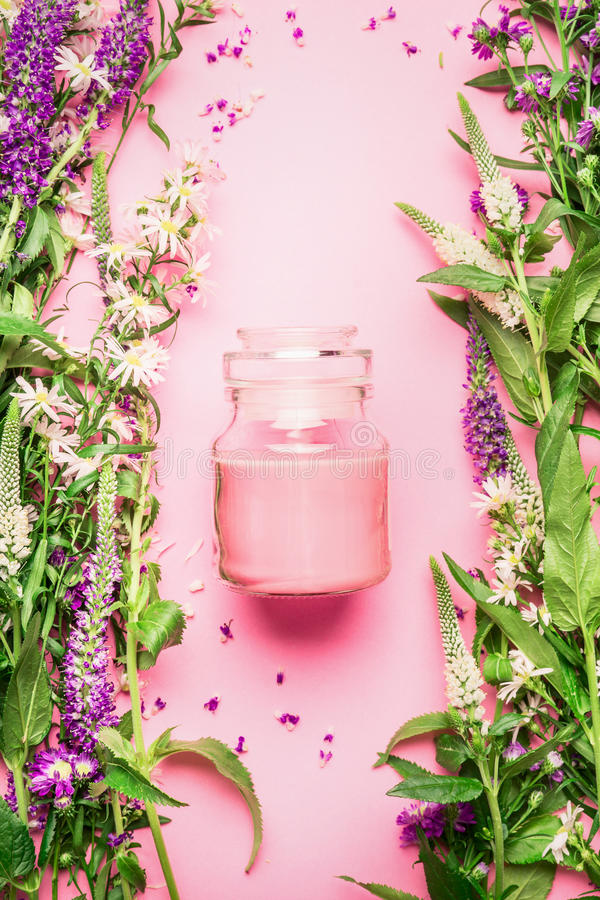 Natural herbal skin care cosmetic concept. Glass jar with cream or lotion and fresh herbs and flowers on pink background, top view stock images