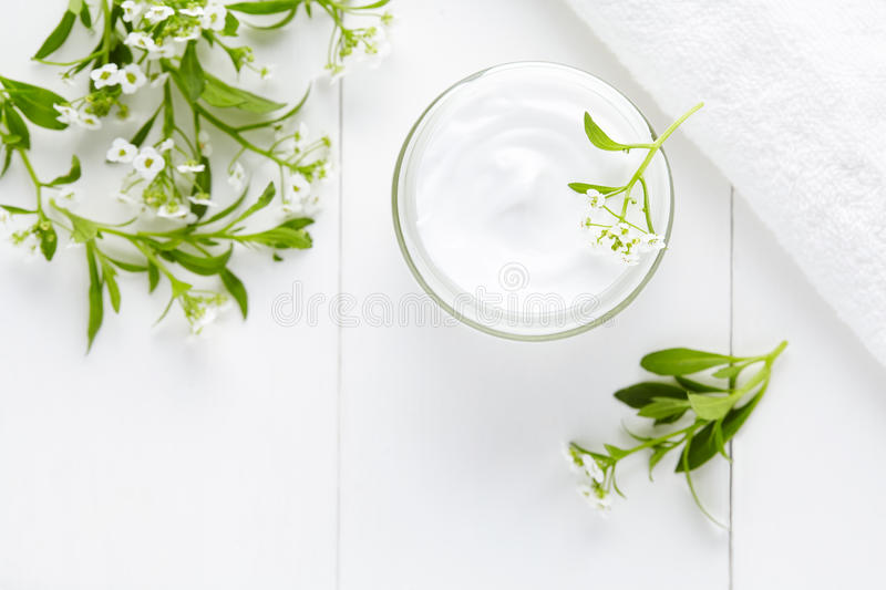 Natural herbal spa cosmetic hygienic cream with flowers skincare product. In glass jar on white background stock images