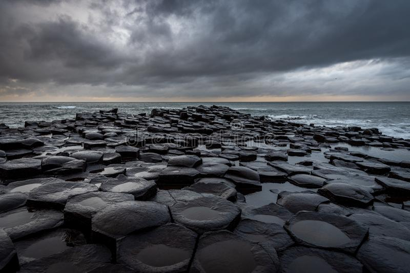 The natural hexagonal stones at the coast called Giant`s Causeway, a landmark in Northern Ireland with dramatic cloudy sky royalty free stock image