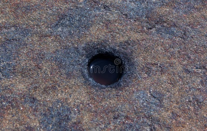 Natural hill stone pit with water texture background. Rural of india, asia royalty free stock photo