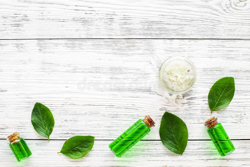 Natural hipoallergenic cosmetics with tea tree essential oil. Oil, lotion, leaves on white wooden background top view stock image