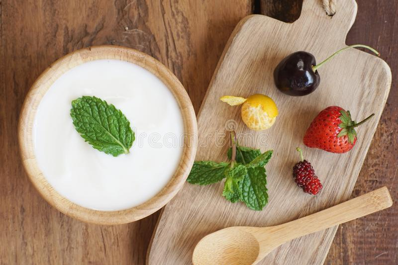 Natural homemade plain organic yogurt mixed with fresh berry fruit white bowl and wood spoon on wood texture background stock image