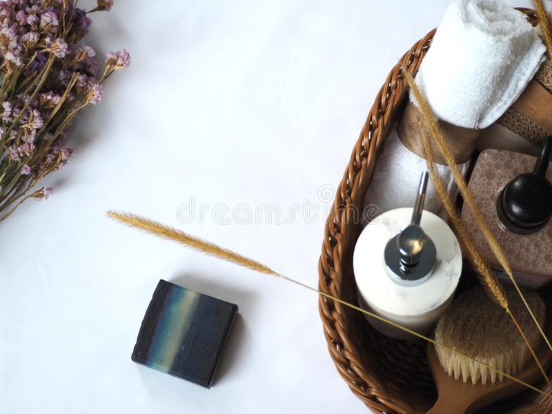 Natural homemade soap and bath accessories in the basket with flower decoration on white background royalty free stock image