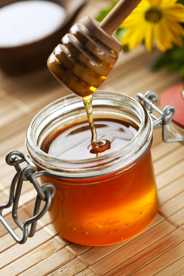 Natural honey. Honey dripping from dripper into a jar, shallow depth of field stock photo