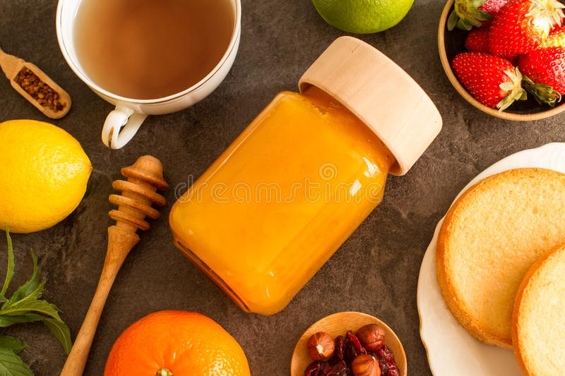 Natural honey in jar with plants. Fresh and dried fruits on a wooden board stock photo