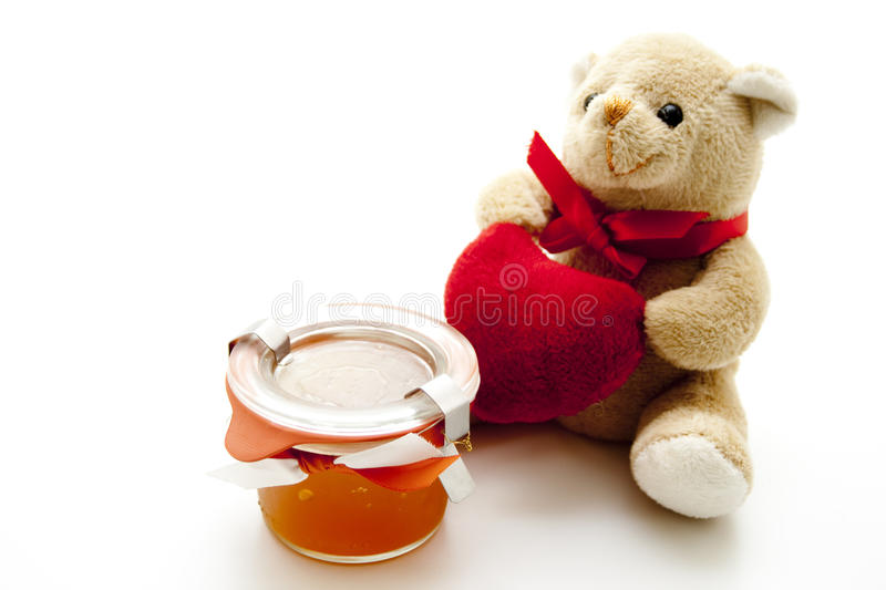 Natural honey plush bear and heart. Natural honey in the glass with plush bear and heart stock photos