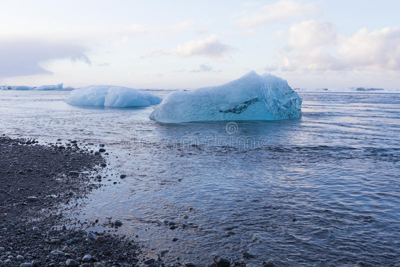 Natural ice breaking from glacier on black sand beach stock photo