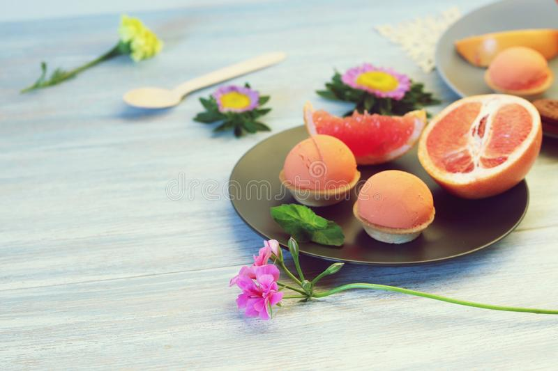 Natural ice cream, sorbet, grapefruit, mint, flowers on a wooden table stock photography