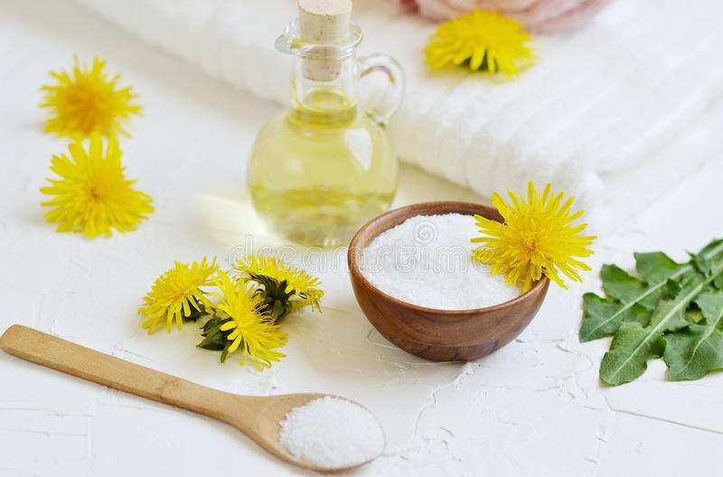 Natural ingredients for homemade body salt scrub with dandelion flowers, lemon, honey and olive oil royalty free stock photo