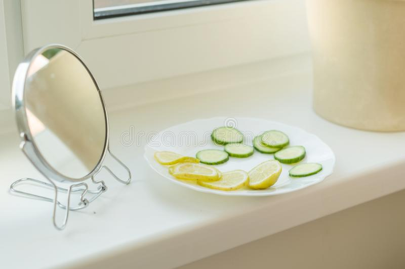 Natural ingredients for homemade masks cucumber and lemon slices on the windowsill at home, with mirror. Skin care, cosmetics,. Cosmetology, dermatology stock photos