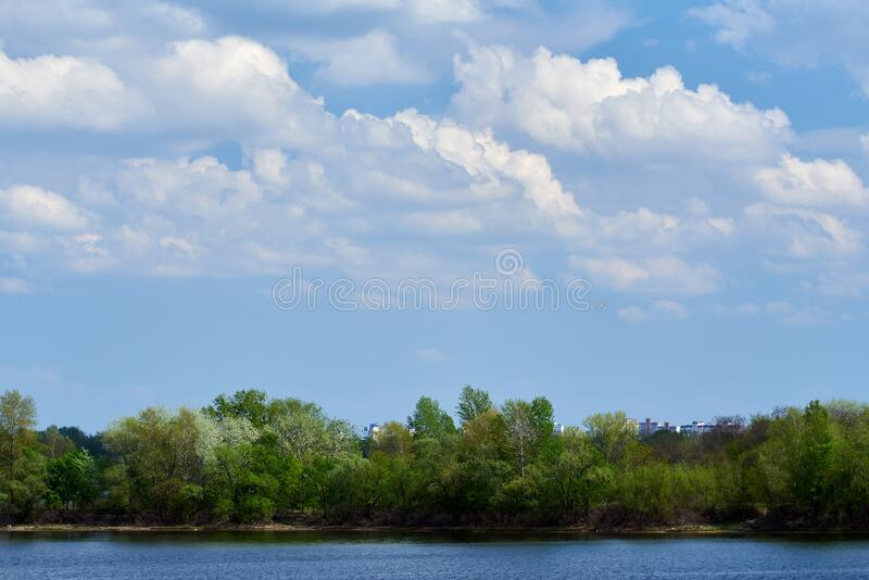 Natural island with green plants, contrasting cloud sky and blue water river Dnepr. Landscape.  stock image