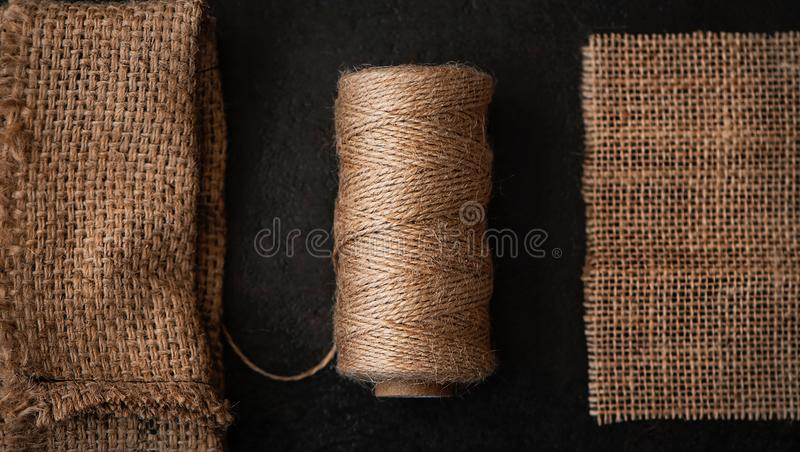 Natural jute twine roll, burlap on black background. Supplies and tools for handmade hobby leisure stock photo