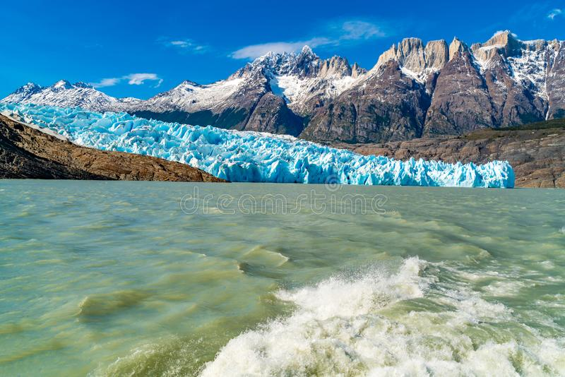 Natural landscape at Glacier Grey with the snowy rock mountain, Lake Grey and water splash behind the ship. At Torres del Paine National Park in Chile royalty free stock photography