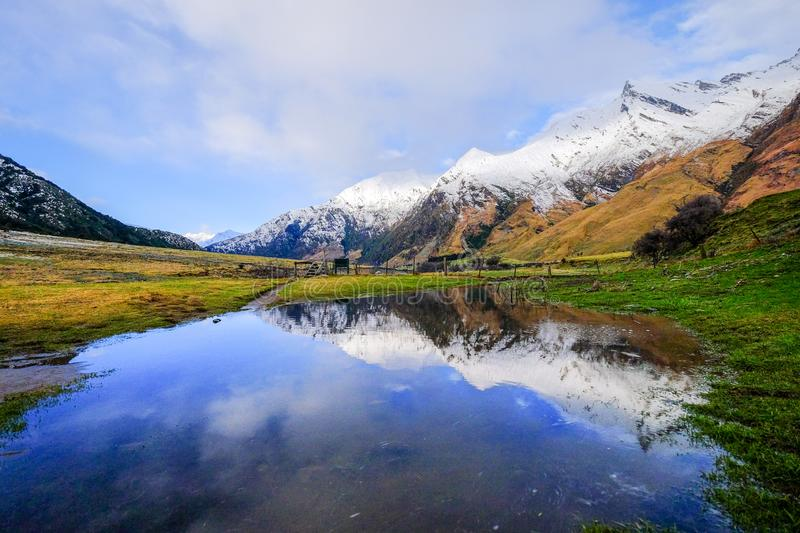Peaceful remote image motivational and inspiration use. Natural landscape image of snow mountain, blue lake, green grass field in New Zealand. Peaceful remote stock image