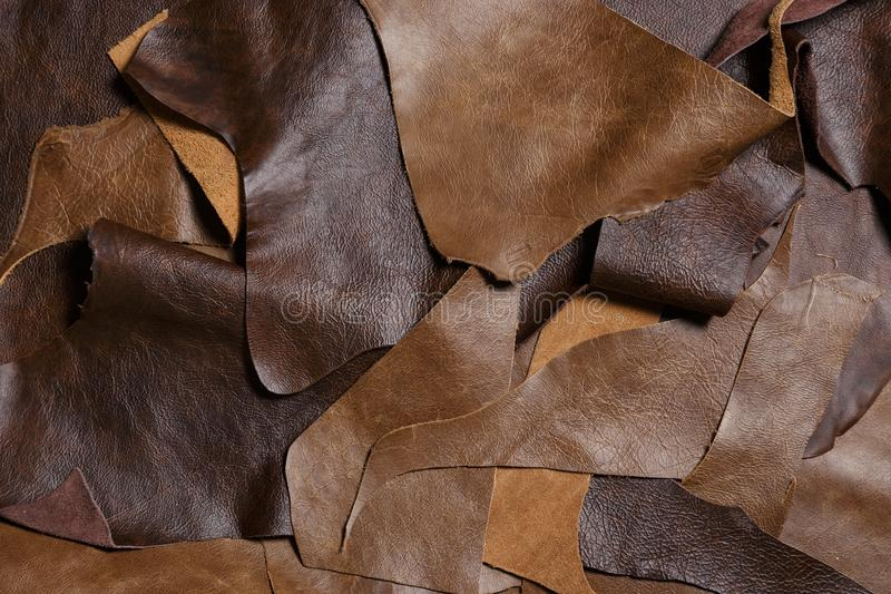 Natural leather in the tailoring workshop. Top view. Many pieces of leather royalty free stock photo