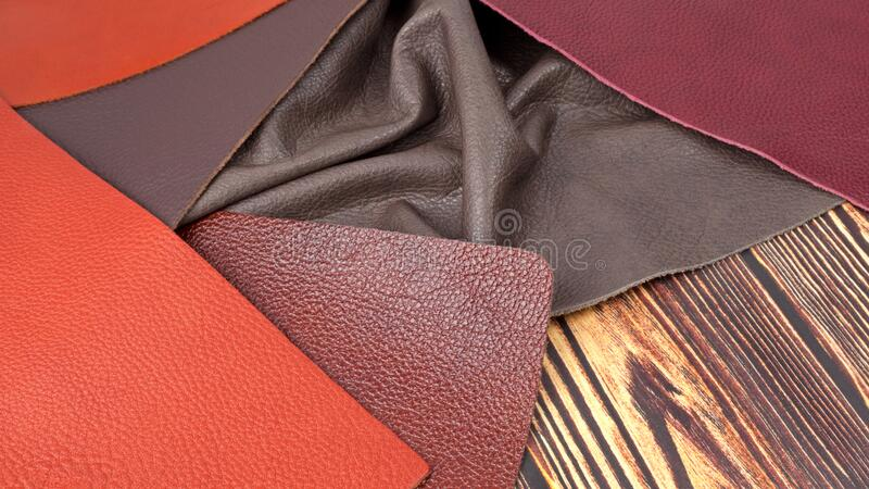 Natural leather textures samples on dark wooden background. Different colors natural leather textures samples on dark wooden background stock image