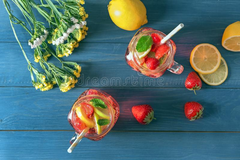 Natural lemonade with strawberries in mason jars on wooden table royalty free stock photos