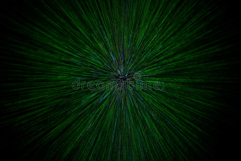 Natural lens zoom explosion radial blurred green particles on black background with selective focus royalty free stock image