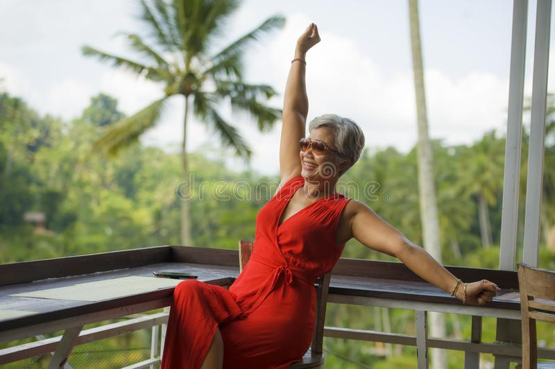 Attractive and happy Asian Indonesian middle aged woman with grey hair relaxed chilling cheerful and carefree and tropical. Natural lifestyle portrait of royalty free stock photo