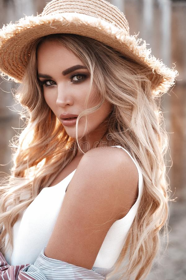 Natural lifestyle portrait of a beautiful appealing young woman with long loose blonde hair in a straw hat. Countryside landscape. At the background. Summertime royalty free stock images