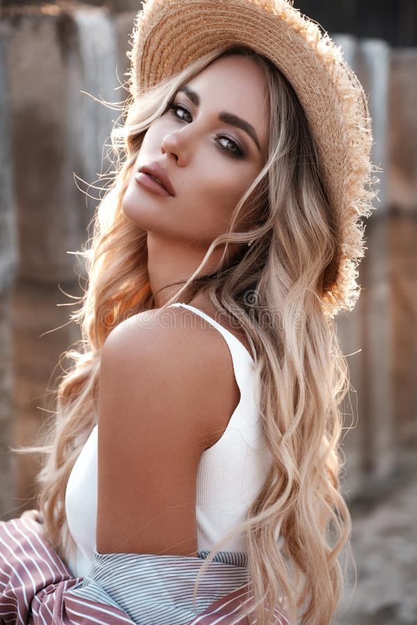Natural lifestyle portrait of a beautiful sexy young woman with long loose blonde hair in a straw hat. Countryside landscape at th royalty free stock image