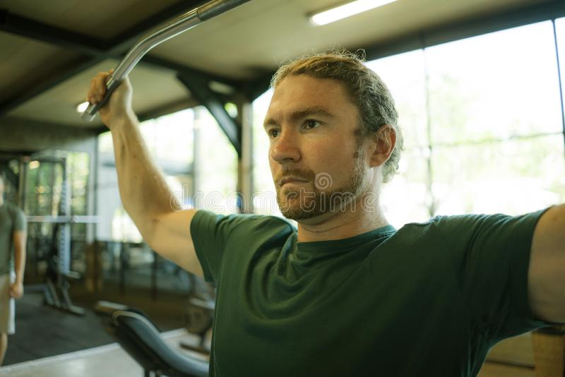 Natural lifestyle portrait of young athletic and attractive man training and body building doing muscular exercise with gym royalty free stock photo