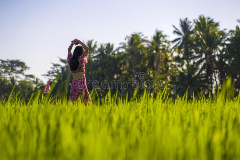 Natural lifestyle portrait of young beautiful and happy Asian Chinese woman in elegant Summer dress walking carefree and relaxed. At fresh tropical rice field stock images