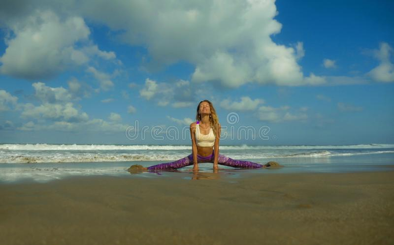 Natural lifestyle portrait of young happy and attractive woman with athletic and fit body doing yoga pose at beautiful beach. Feeling harmony and tranquility in stock photography