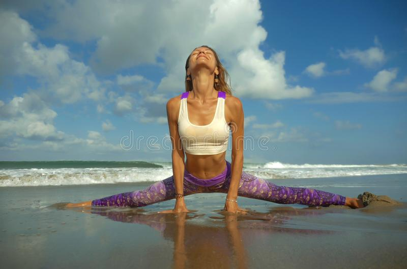 Natural lifestyle portrait of young happy and attractive woman with athletic and fit body doing yoga pose at beautiful beach. Feeling harmony and tranquility in stock photos