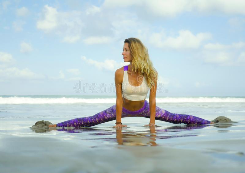 Natural lifestyle portrait of young happy and attractive woman with athletic and fit body doing yoga pose at beautiful beach. Feeling harmony and tranquility in royalty free stock photos