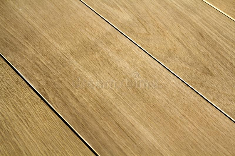 Natural light brown wooden parquet floor boards. Sunny soft yellow texture, copy space perspective background stock photo