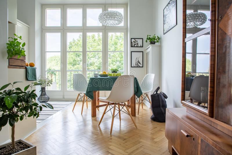Natural light coming through glass door from balcony into a stylish kitchen room interior with white chairs around a wooden dining. Table royalty free stock photos