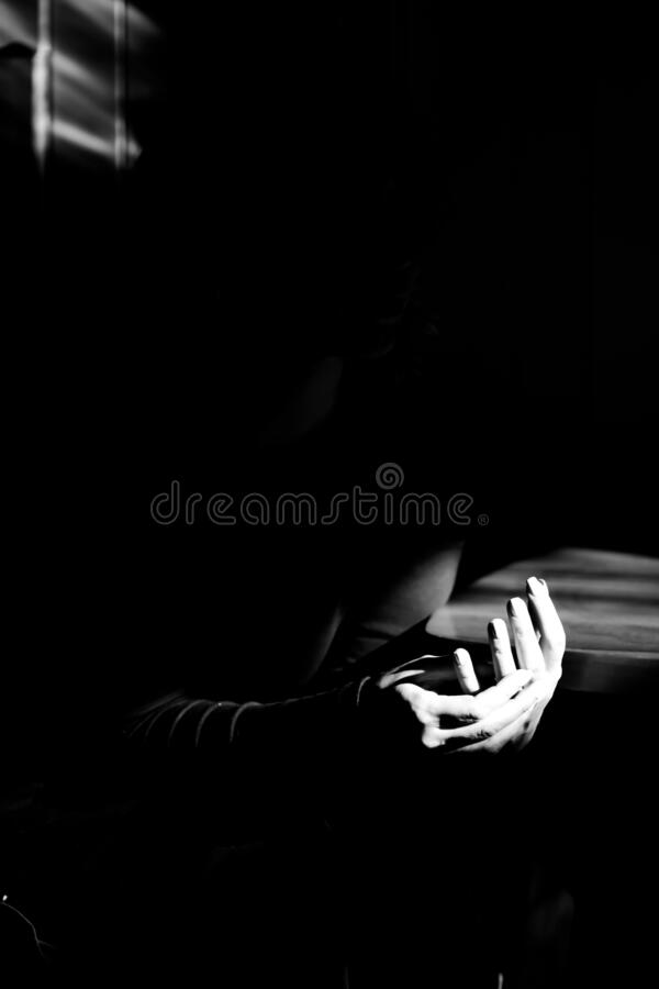 Hands of woman in sunlight. Black and white high contrast photo. stock image