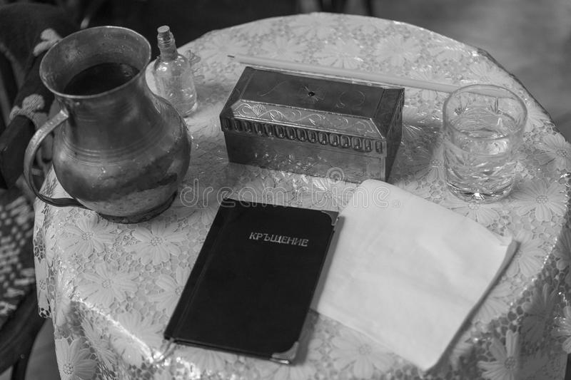 Accessories of a priest for Christian baptism in black and white. Natural light in a small Christian church and a light grain effect stock photography