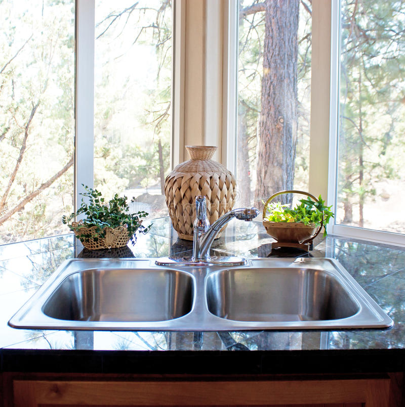 Natural Lighting Stainless Kitchen Window and Sink. A beautiful light and airy naturally lit stainless kitchen sink in front of a lovely forest window stock images