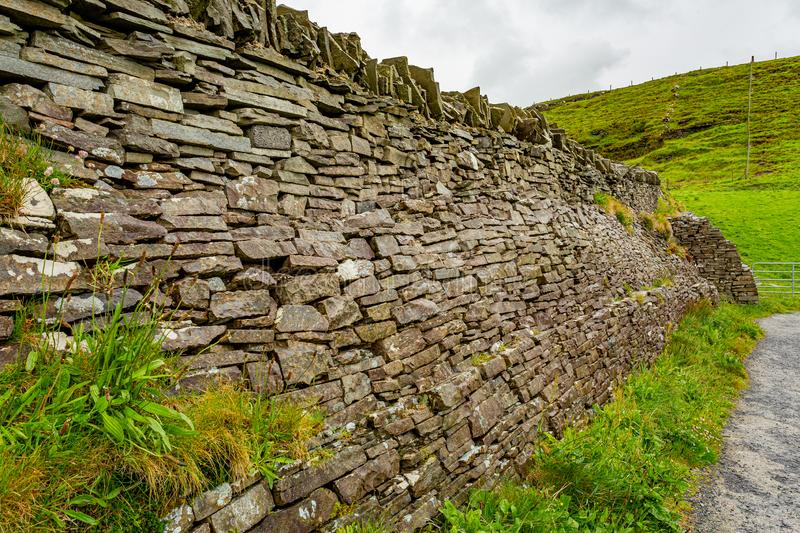 Natural limestone wall next to a path in the Burren. Geosites and geopark, spring day in the countryside in County Clare in Ireland royalty free stock photography