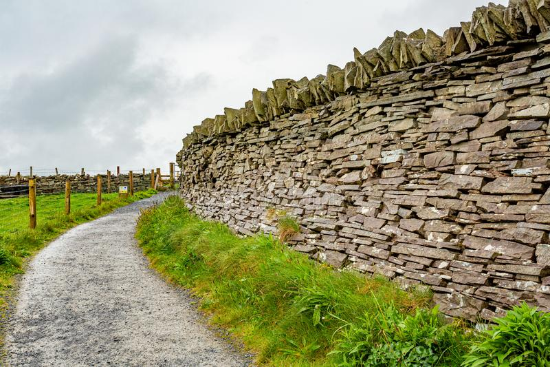 Natural limestone wall next to a path with fence of wooden poles and wire in the Burren. Geosites and geopark, spring day in the countryside in County Clare in stock images