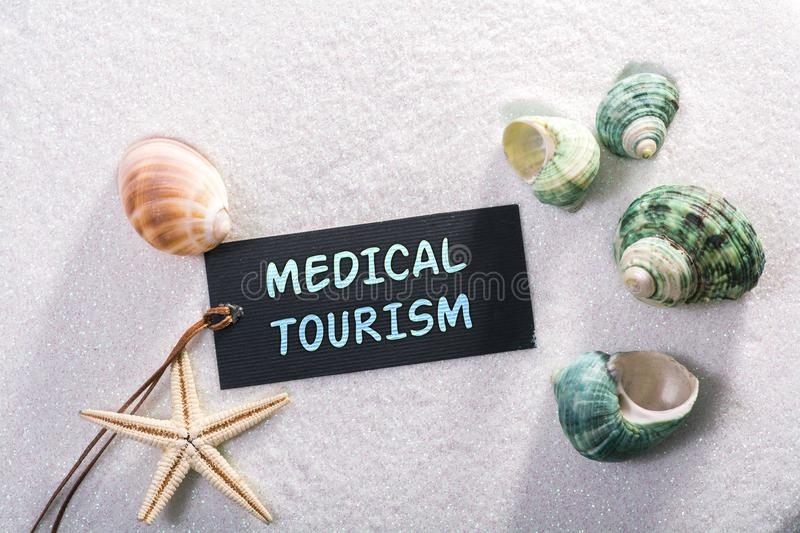 Label with medical tourism. A natural looking label with medical tourism written on it with sand and seashell and star royalty free stock photo