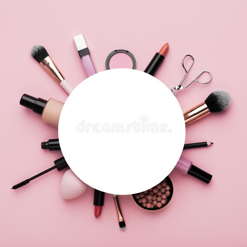 Natural makeup cosmetics around white blank sheet of paper. For promotion or logo on pink background royalty free stock image