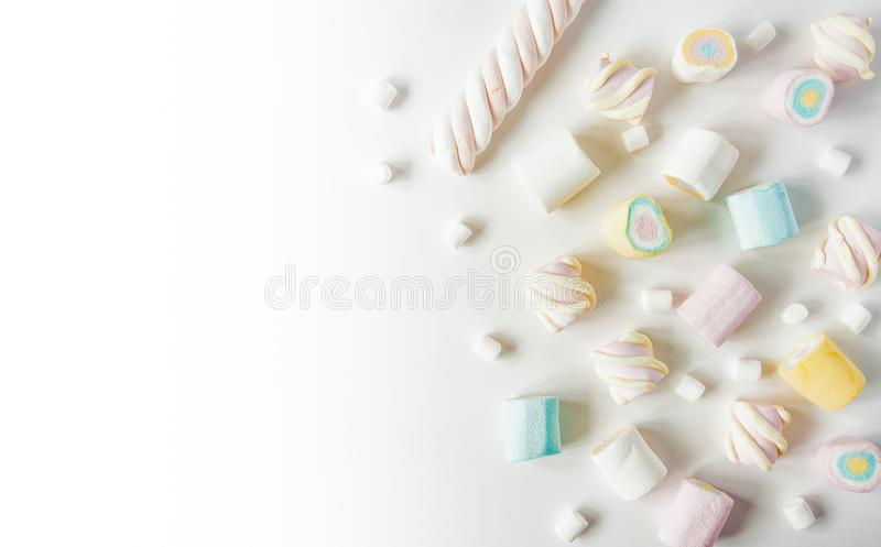 Natural marshmallows sweets on a white background. Airy multicolored marshmallows sprinkled on the table stock photos