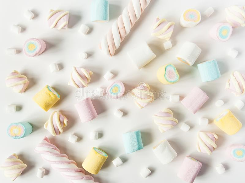Natural marshmallows sweets on a white background. Airy multicolored marshmallows sprinkled on the table royalty free stock photo