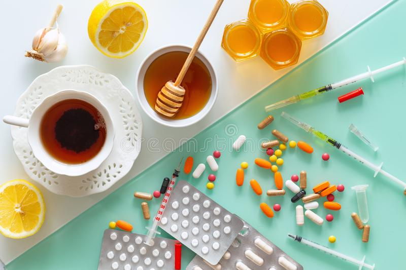 Natural medicine, tea, honey, lemon and garlic against tablets of syringes and other medications, top view background in two color royalty free stock photography