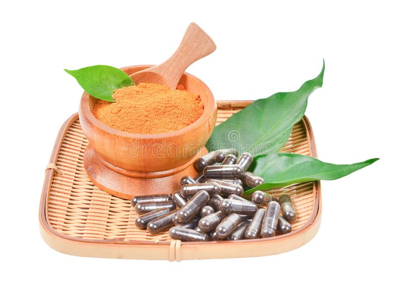 Natural medicine capsule pill with black herb, and wooden mortar stock image